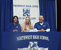 Megan Ramsey of Northwest High School, center, smiles during her signing ceremony. Pictured are, from left, Northwest High School Volleyball Coach Debbie Fortner, Megan Ramsey and Lewis and Clark Community College Volleyball Coach Jim Hunstein.